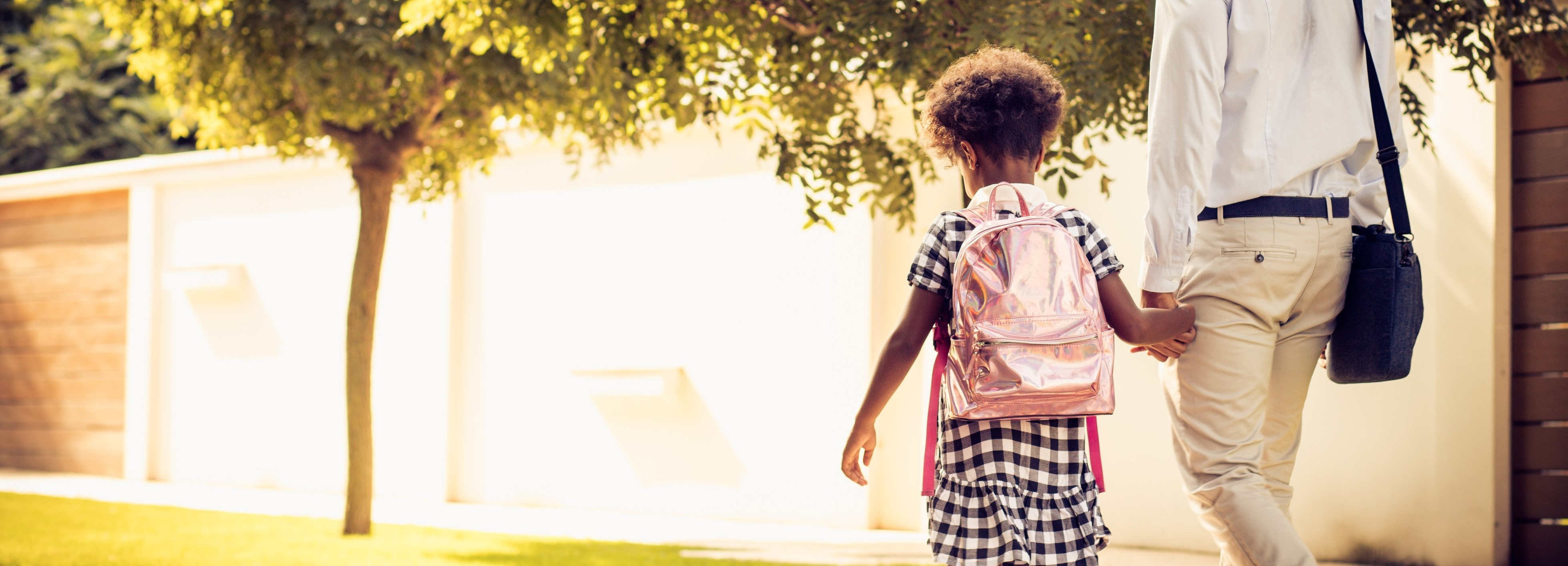 Girl wearing pink sparkly back pack walking hand-in-hand with her father