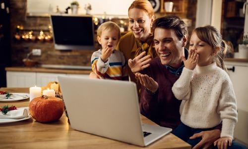 family waving and blowing kisses at a virtual gathering