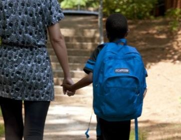 a young boy walking to school with his mother
