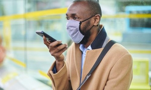 Man wearing mask on phone waiting for train