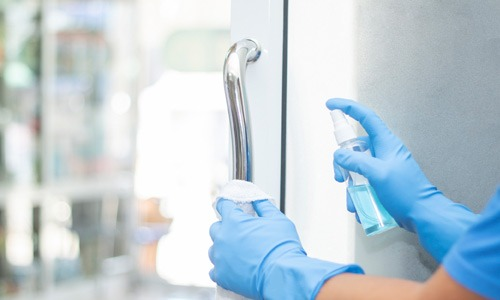 person cleaning glass door with spray cleaner