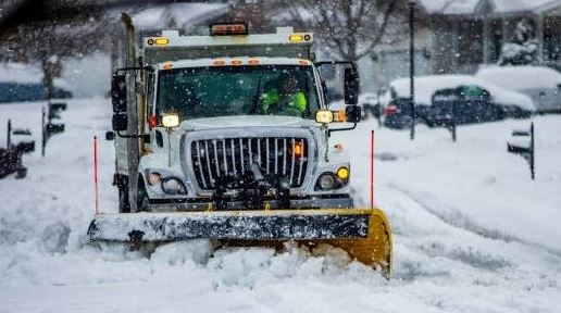 Snow plow clearing a street during a winter storm.