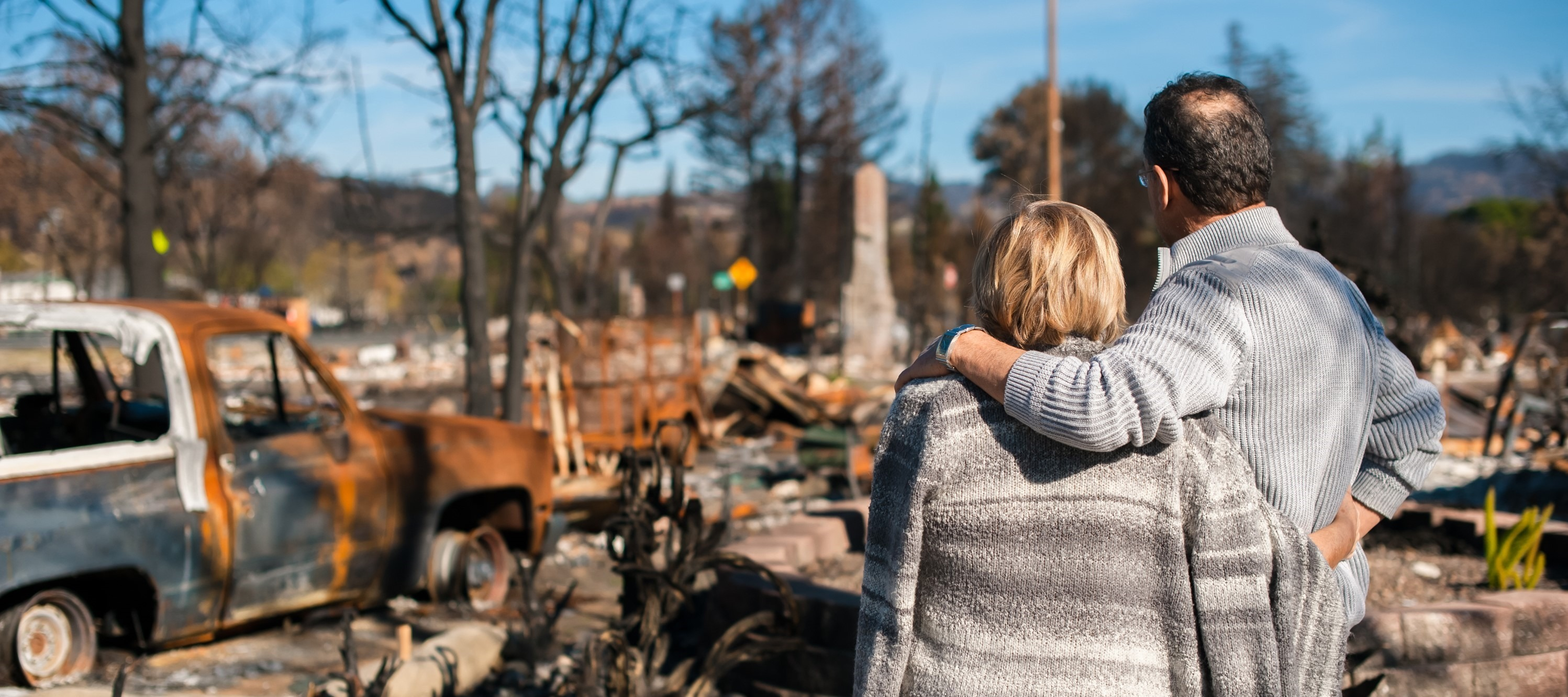 A man and woman stand arm-in-arm overlooking the remains of their house and neighborhood after a disaster.